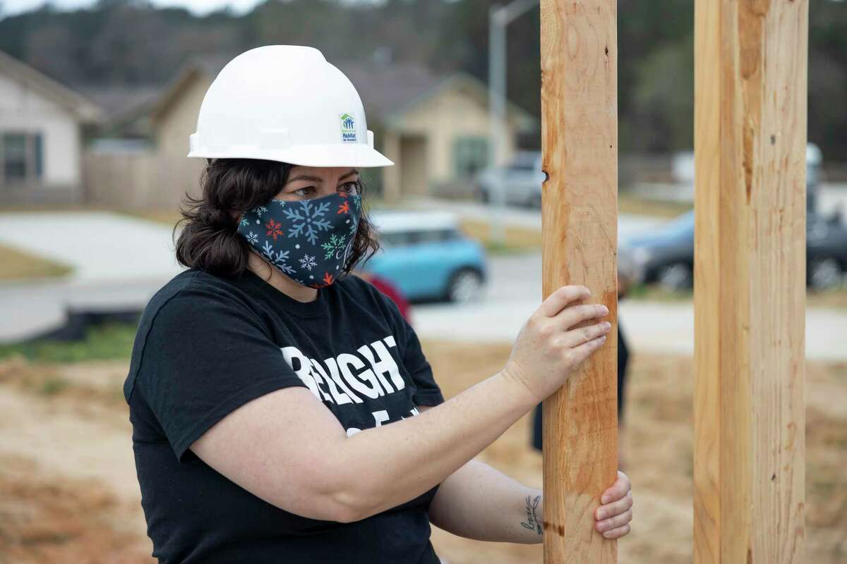 Deanna Fallin secures one of the walls of her future home during a home building reveal hosted by Habitat for Humanity of Montgomery County, Saturday, March 13, 2021, in the Cedar Creek Community of Conroe. Fallin has never owned a home before and has lived at the Women's Shelter for the last two and a half years.