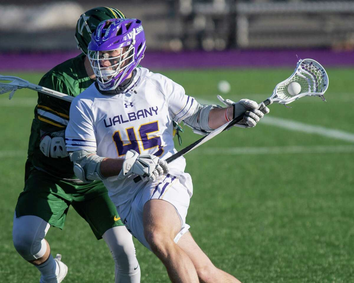 UAlbany sophomore Graydon Hogg heads up field in front of Vermont sophomore JJ Levandowski at John Fallon Field on the UAlbany campus in Albany, NY, on Saturday, March 13, 2021 (Jim Franco/special to the Times Union.)