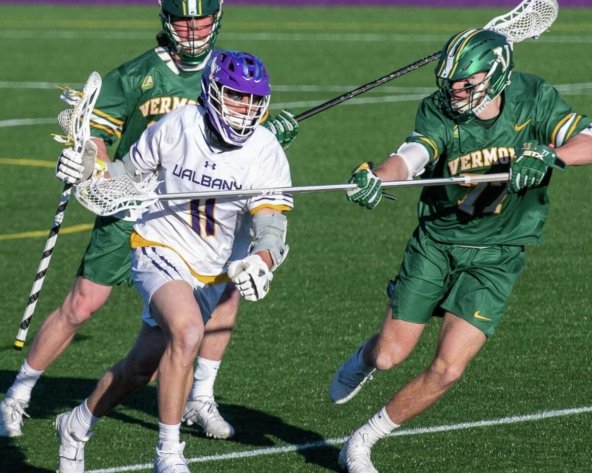 UAlbany junior Corey Yunker takes a stick check by Vermont sophomore Nick Alviti at John Fallon Field on March 13. It was the first of two meetings the Danes had with the Catamounts, and Vermont won 14-12 in this one. (Jim Franco/Special to the Times Union)
