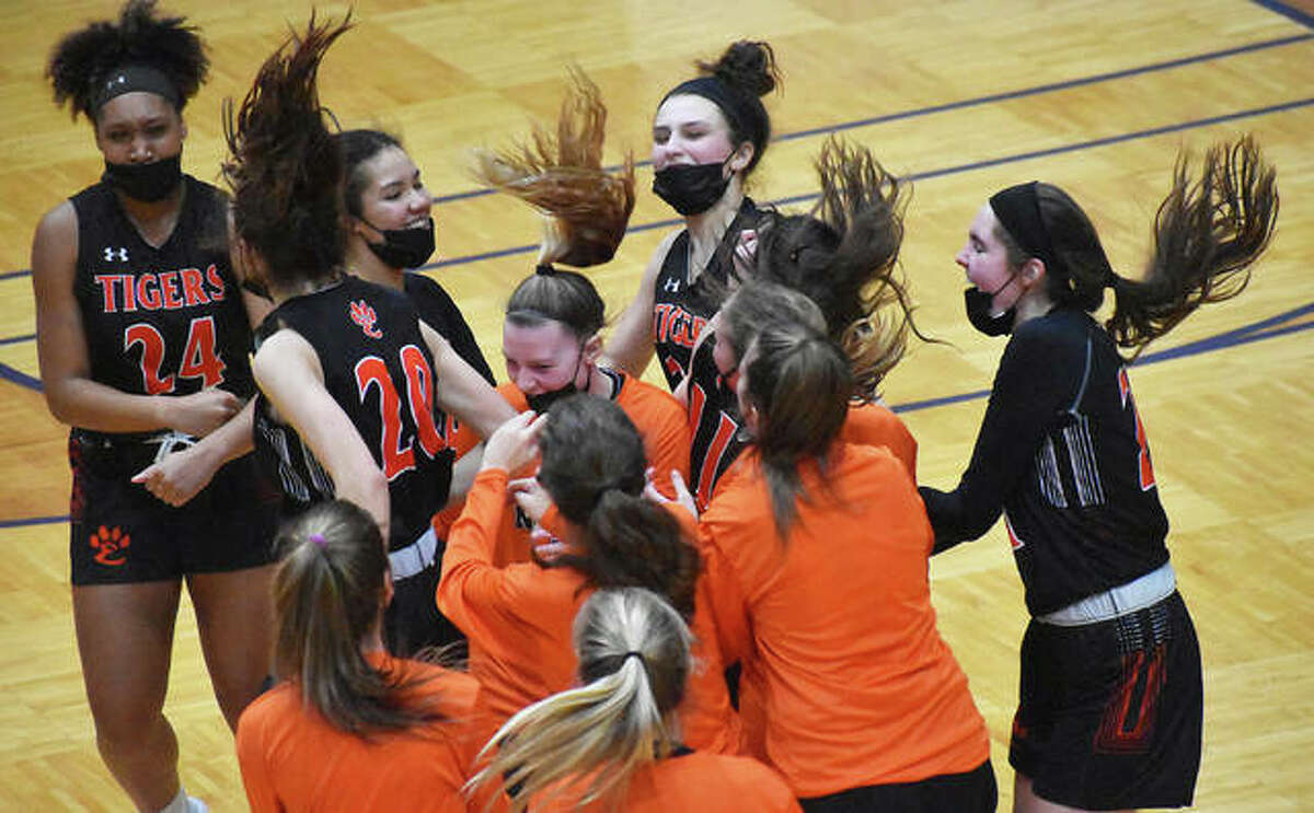 The Edwardsville Tigers celebrate after beating O'Fallon 57-45 on Saturday to claim their 12th straight Southwestern Conference championship.