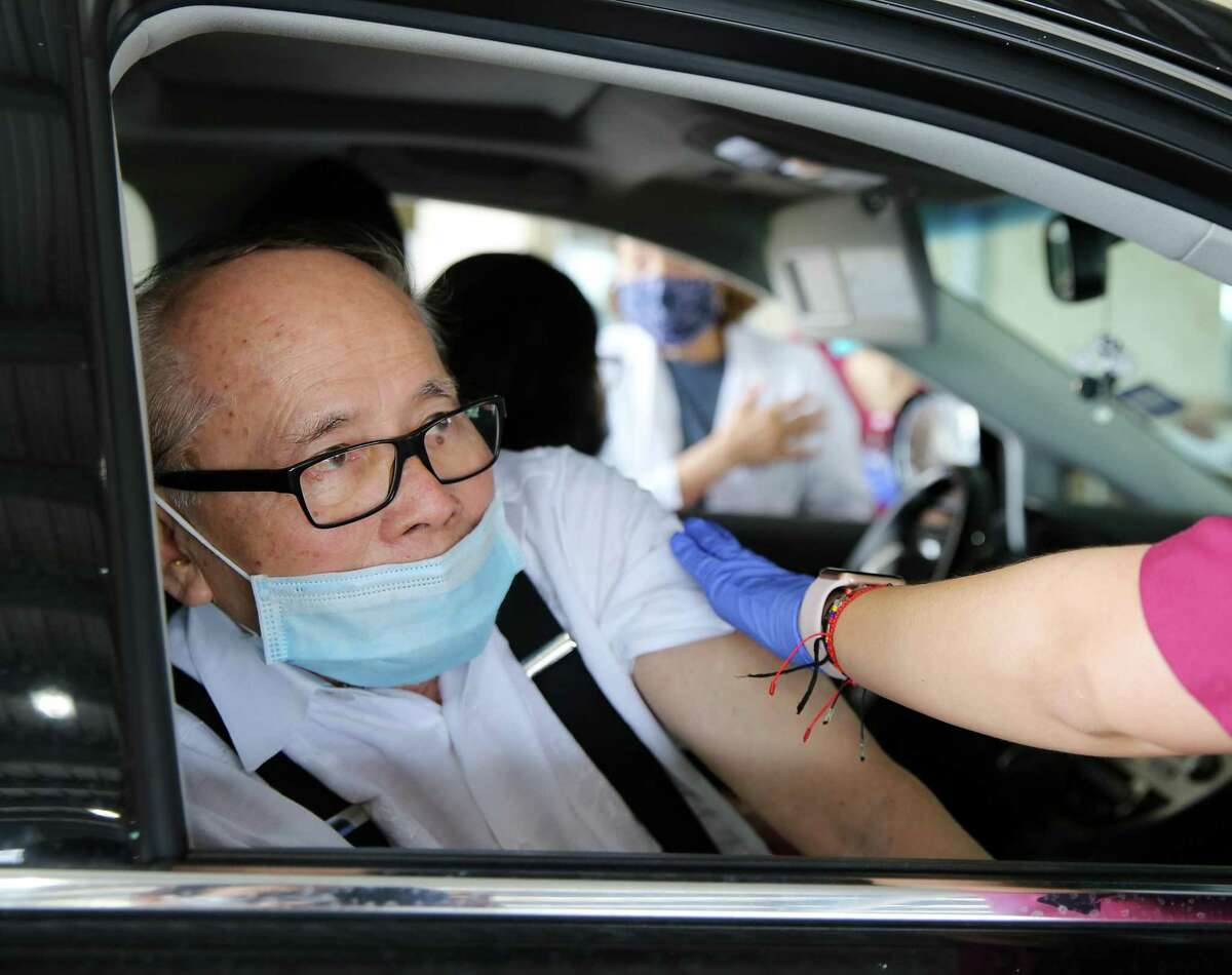 Nhuan Le looks at a nursing student from Texas Woman's University, after getting his vaccine during a drive-thru vaccination site hosted by the Vietnamese Culture and Science Association and the Vietnamese American Medical Association in Houston on Saturday, March 13, 2021.