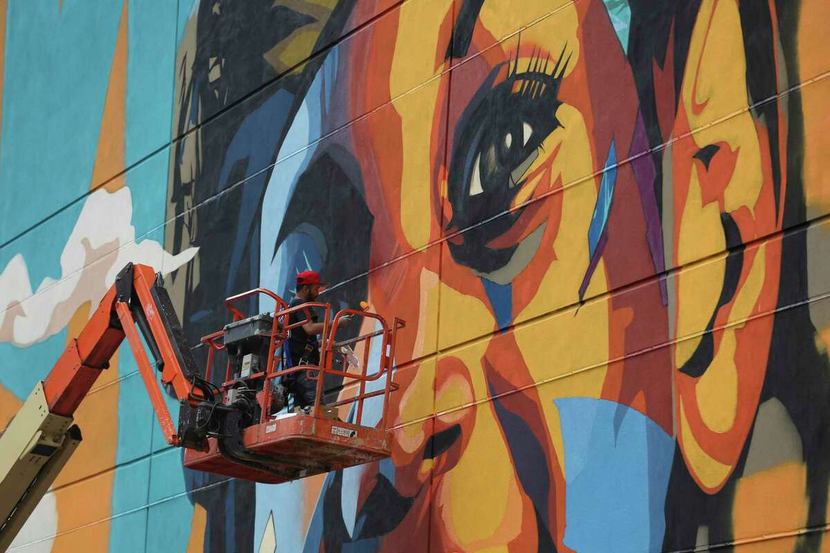 """Artist Satoshi """"Dragon76"""" Fujita works Wednesday on the """"Zero Hunger"""" mural, one of the largest in the city. The mural aims to """"mobilize action to combat global food insecurity."""""""