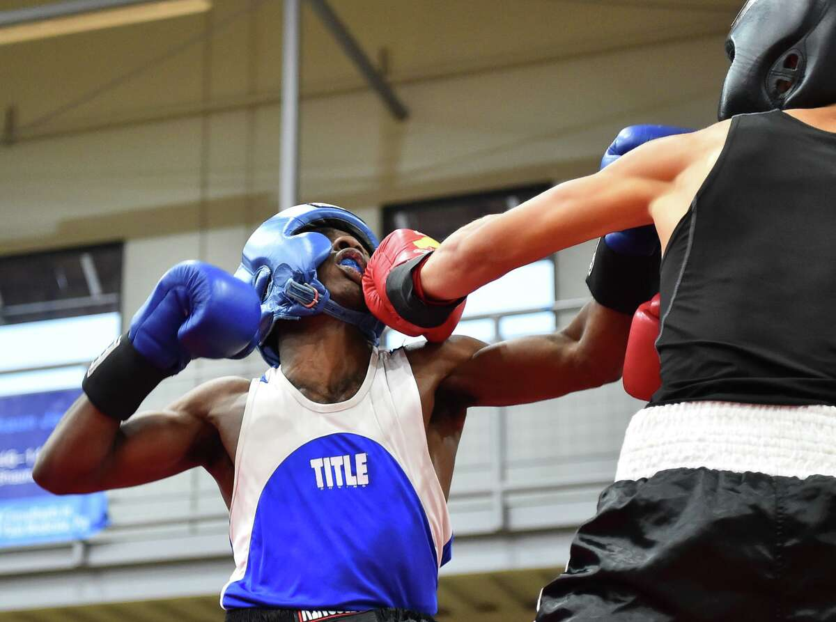 Trevon Fennell takes a punch on the chin from Edward Uhl during the Golden Gloves Finals Saturday at the George Gervin Wellness Center.
