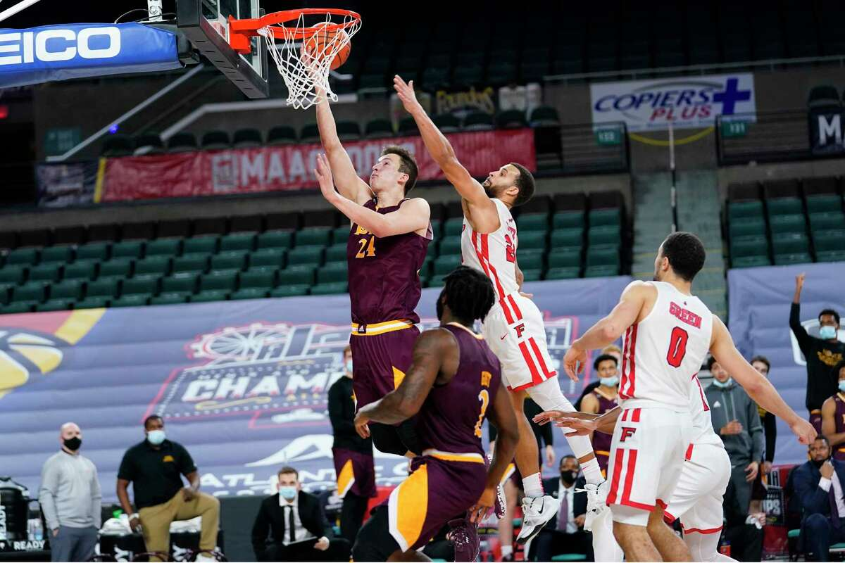 Iona's Dylan van Eyck, left, goes up for a shot past Fairfield's Jesus Cruz in the second half during the finals of the MAAC tournament Saturday in Atlantic City, N.J.