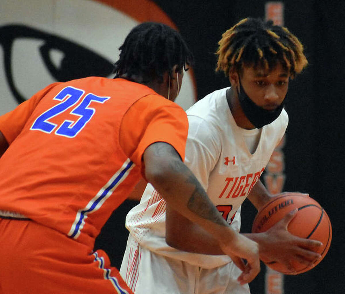 Edwardsville's Jalil Roundtree shields the ball away from an East St. Louis defender during the third quarter of Saturday's game in Edwardsville.