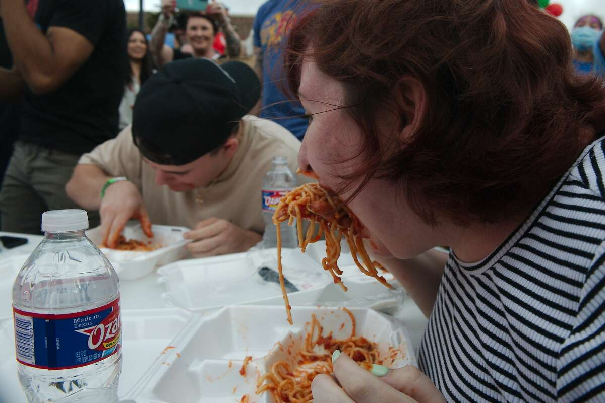 CJ Crider and Brittany Calhoun compete for second place in the spaghetti eating contest during the Dickinson Little Italy Festival Saturday at Water Grove Event Venue in Dickinson.