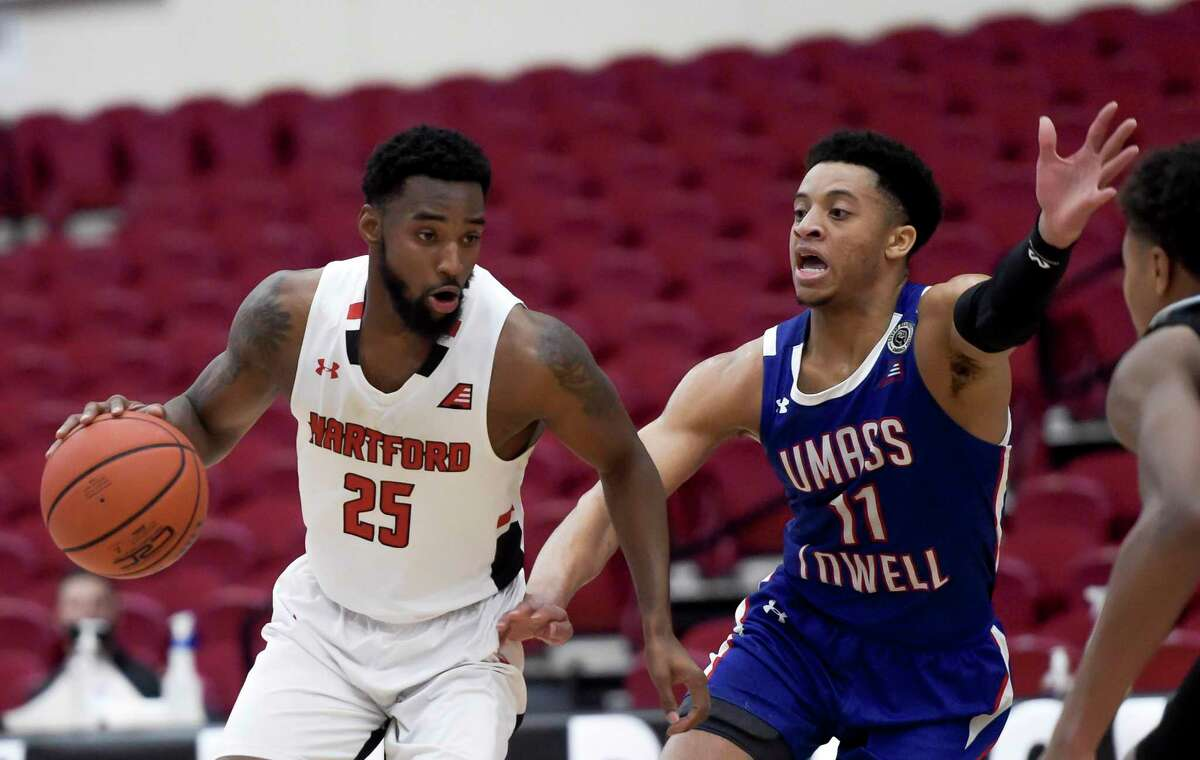 Hartford's Traci Carter (25) is guarded by UMass-Lowell's Obadiah Noel (11) during their America East Conference Tournament championship game Saturday in Hartford.