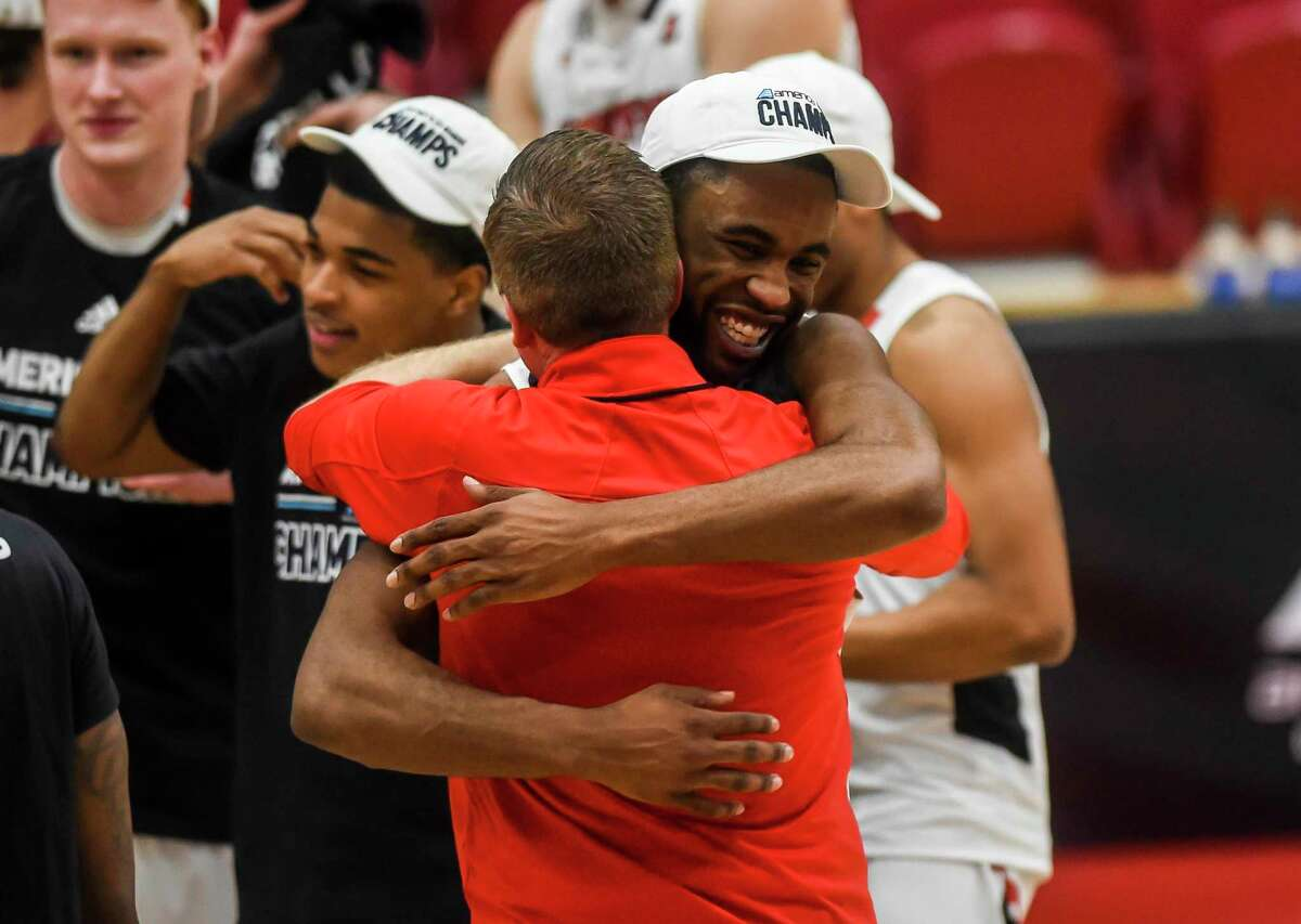 Hartford's Austin Williams (20) and head coach John Gallagher embrace after beating UMass-Lowell in an NCAA college basketball game in the championship of the America East conference tournament, Saturday, March 13, 2021, in Hartford, Conn. (Kassi Jackson/Hartford Courant via AP)