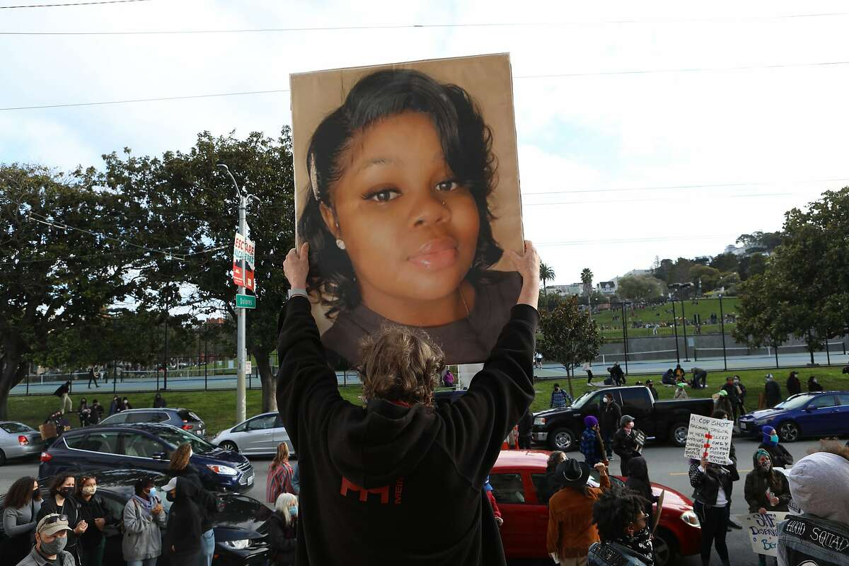 Ken Lundgreen holds an image of Breonna Taylor during a rally and march outside Mission Migh School honoring the police shooting victim.