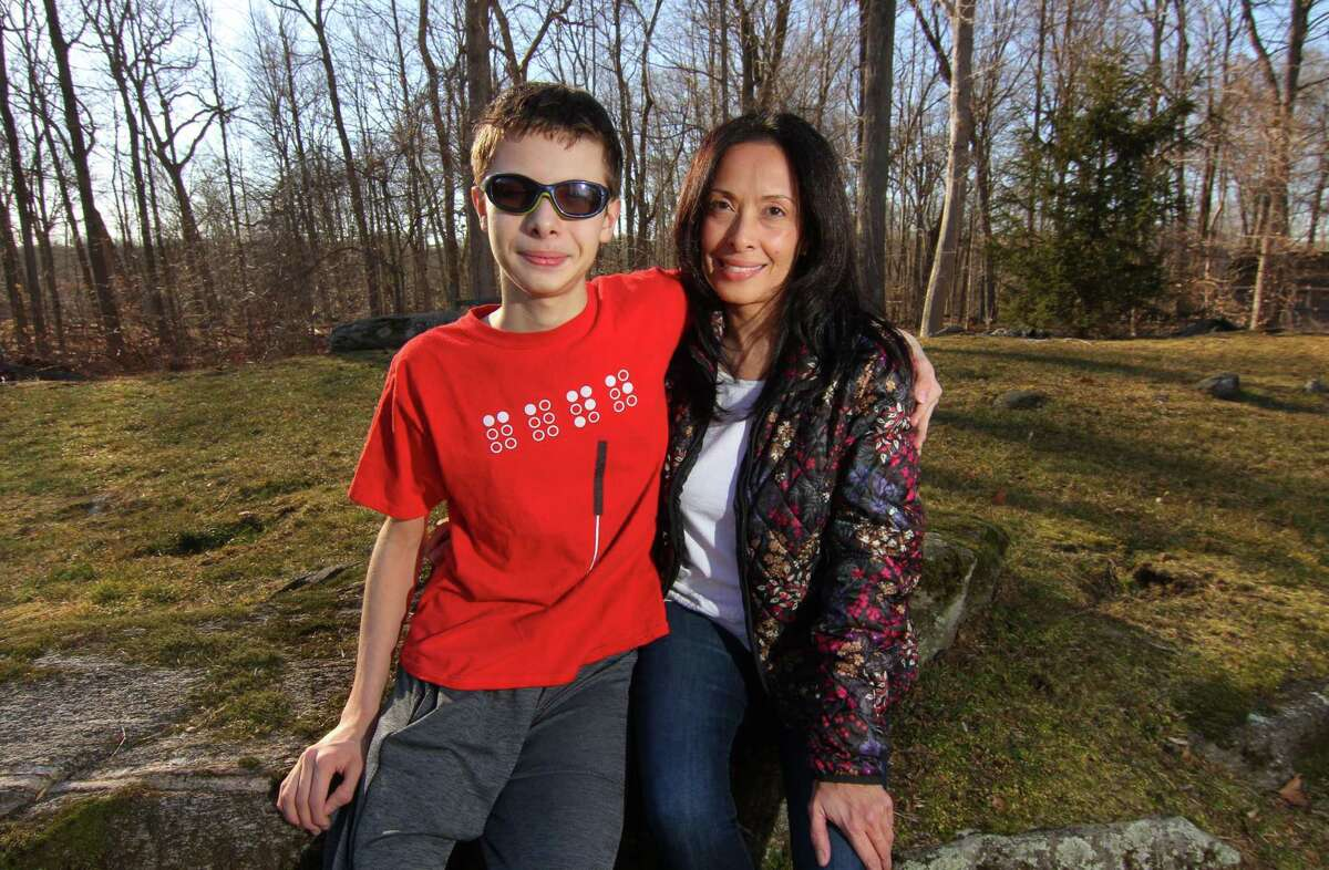 Mabel Balestra and her son Pierluca, 14, who is legally blind, pose together at their home in Greenwich, Conn., on Friday Mar. 12, 2021. Balestra recently won a state complaint against the district alleging that Greenwich Public Schools failed to provide adequate special education services. Balestra is using the success of that case to try to bring more sweeping change to the district's special education services and provide better access for all students.
