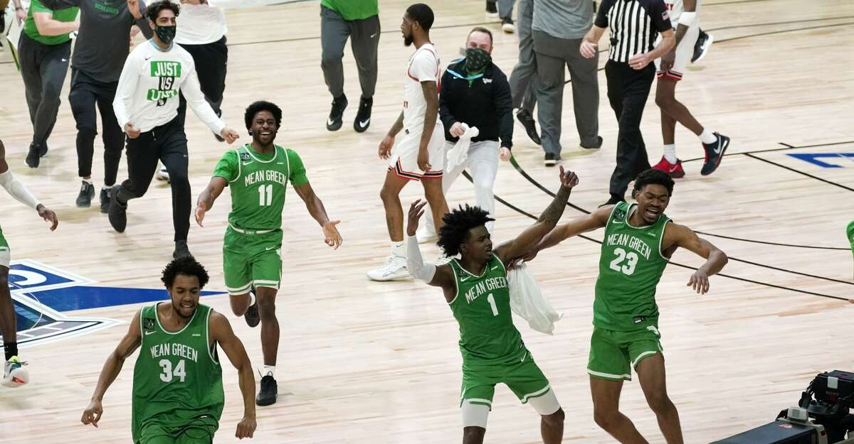 North Texas players celebrate after the championship game against Western Kentucky in the NCAA Conference USA men's basketball tournament Saturday, March 13, 2021, in Frisco, Texas. North Texas won 61-57 in overtime. (AP Photo/Tony Gutierrez)