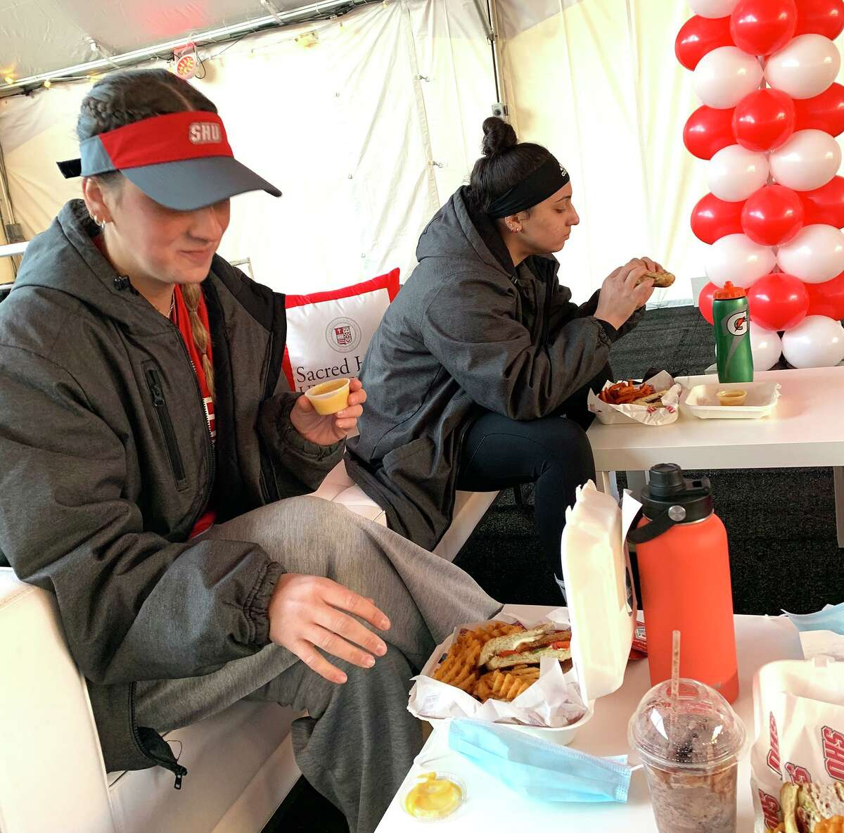 Sacred Heart University students gather in an outdoor tent with 3,500 square feet of space for them to socialize as the school relaxes some of its COVID restrictions.