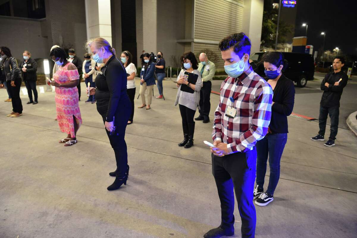 Nathan Acevedo (right), other hospital staff and guests stand a safe 6 feet apart as they pray during a candlelight vigil Saturday night at Methodist Hospital on the Northwest Side. The hospital has treated more than 3,200 people with COVID-19 since the pandemic began one year ago. Most recovered but others died because of the virus, prompting the remembrance ceremony.