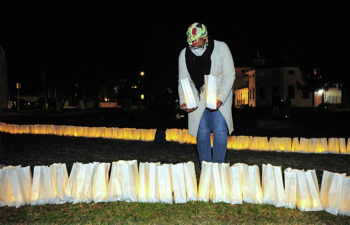 Area resident Wisenite Laurent places two luminaria to remember her mother and an aunt who died from COVID-19 during a memorial to mark the one-year anniversary of COVID-19 in Connecticut on Veterans Green in Westport, Conn., on Saturday Mar. 13, 2021. The 2,000 luminaria, placed on the green by members of Green's Farms Church in Westport, honor the more than 2,000 Fairfield County residents who have lost their lives to COVID-19 so far.
