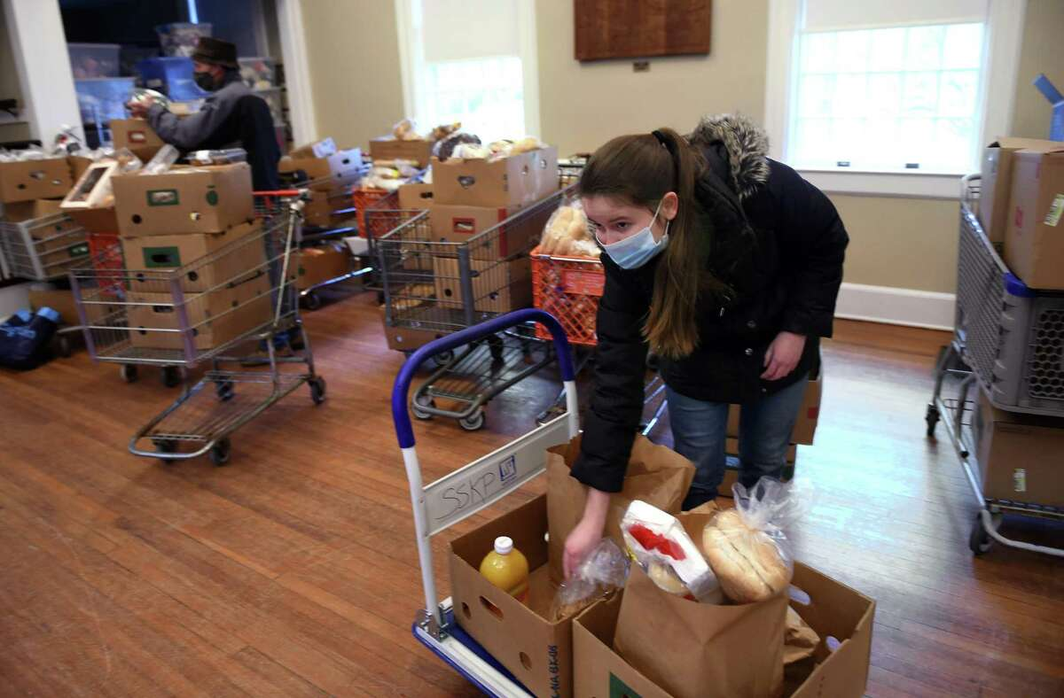 Clare Kenny of Old Lyme prepares bags of groceries at a Shoreline Soup Kitchens & Pantries location at the First Congregational Church in Old Lyme on February 27, 2021.