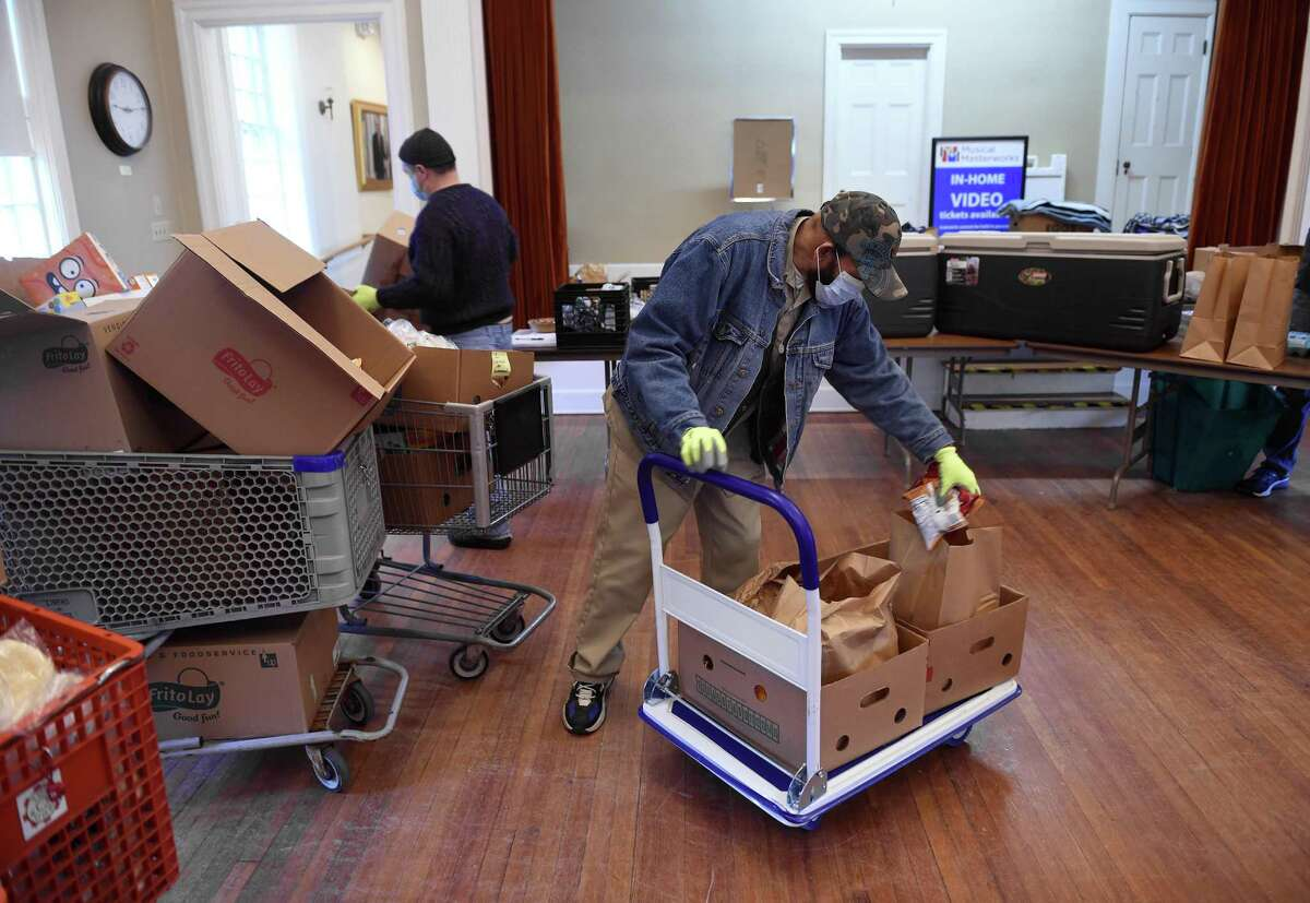 William Jackson of Waterford prepares bags of groceries at a Shoreline Soup Kitchens & Pantries location at the First Congregational Church in Old Lyme on February 27, 2021.