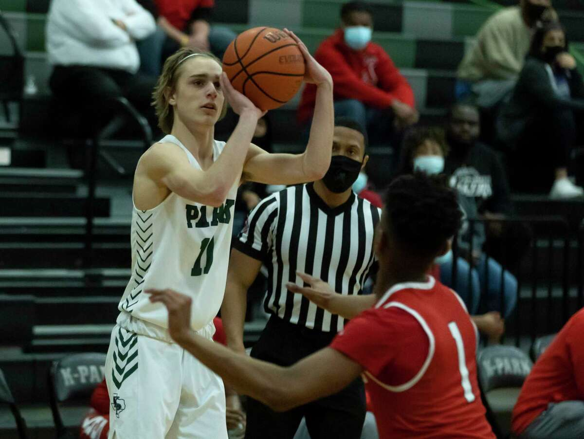 Kingwood Park Jack Keller (11) shoots for a 3-pointer while under pressure from Cleveland guard Tyler Spencer (1) during the first quarter of a 20-5A District basketball game at Kingwood Park High Schoollast month in Kingwood.