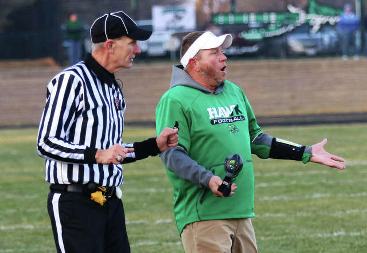 Carrollton coach Nick Flowers (right) questions a call during a 2019 playoff game in Athens. The Hawks are one of four teams in the WIVC who have players quarantined. The conference will adjust its schedule so the short-handed teams face each other in Week 1.