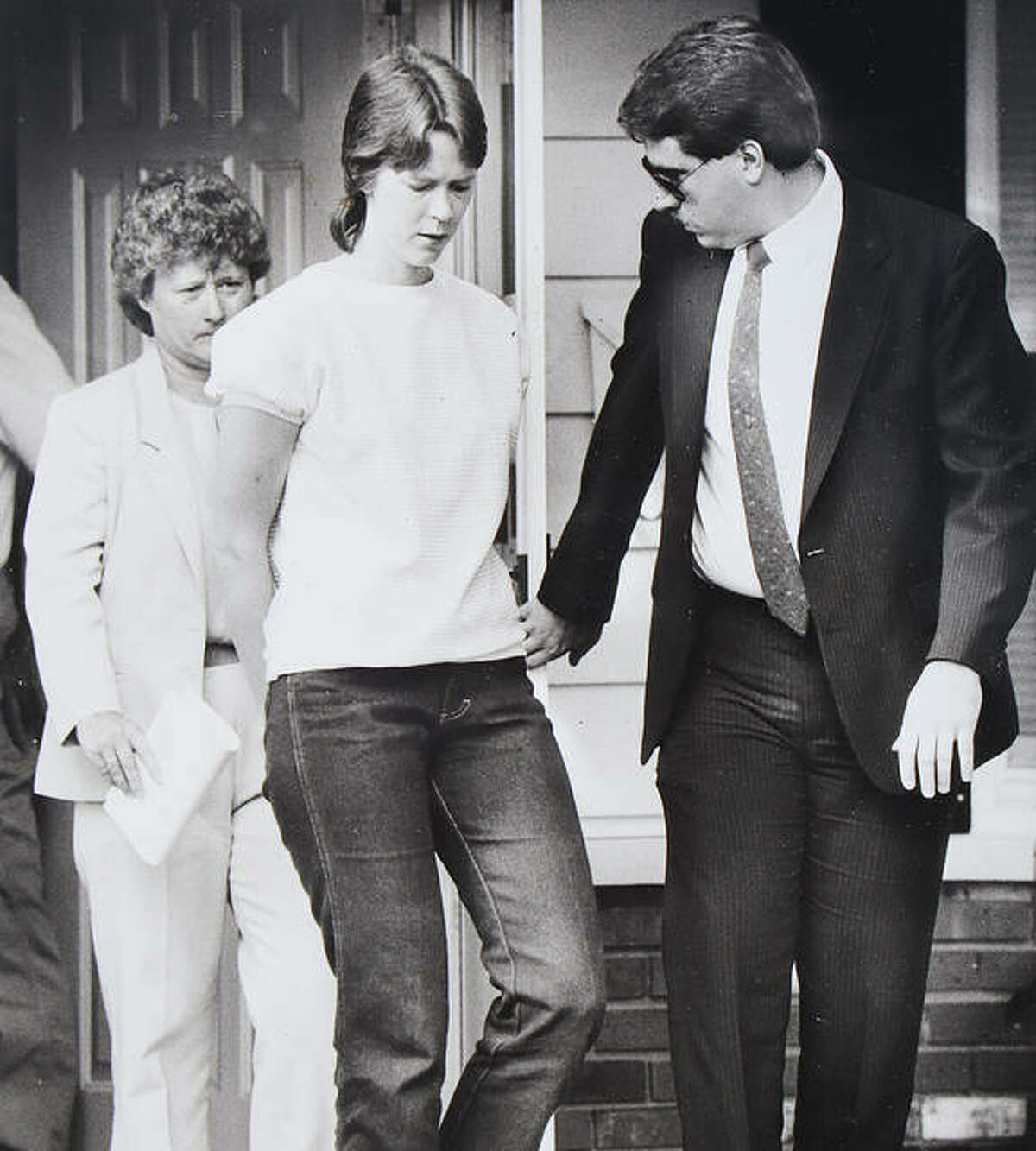 Paula Sims is escorted from the Cottage Hills home of her parents, Orville and Nylene Blew, after she was indicted by a Madison County grand jury.