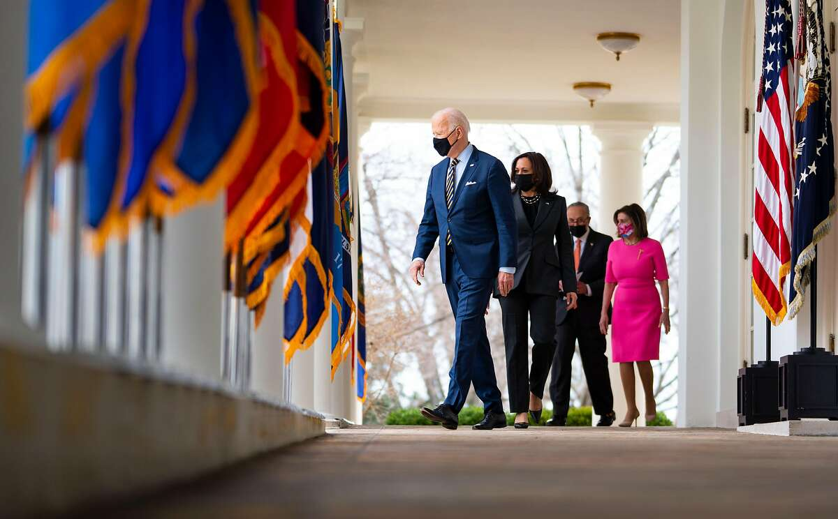 President Biden (left), Vice President Kamala Harris, Senate Majority Leader Chuck Schumer, R-N.Y., and Speaker of the House Nancy Pelosi, D-San Francisco, prepare to deliver remarks on Friday about the stimulus package.