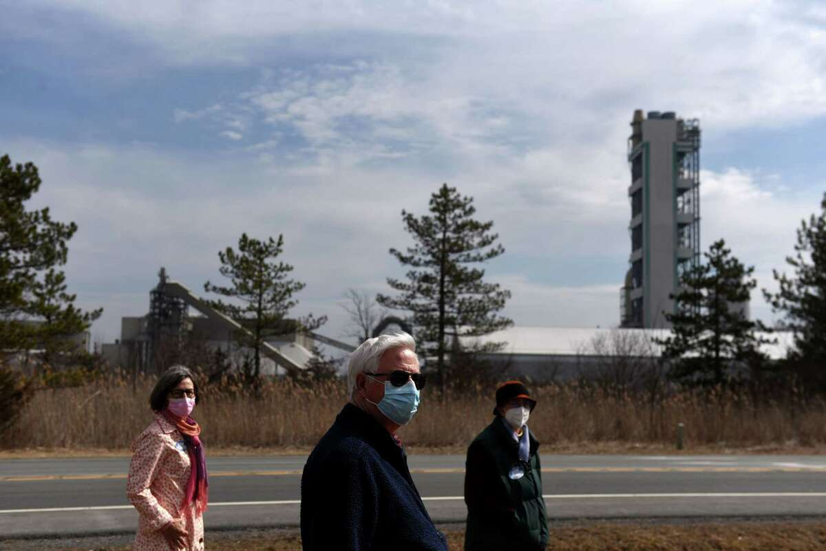 Clean Air Coalition of Greater Ravena and Coeymans members; Christine Primomo, left, Ray Kottke, center, and Barbara Heinzen, right, stand within view of the LafargeHolcim cement plant on Route 9W on Thursday, March 11, 2021, in Ravena, N.Y. New Yorkers will have a chance to vote on the Green Amendment in November 2021, which would put a guarantee for all residents to live in a health environment in the state constitution.(Will Waldron/Times Union)
