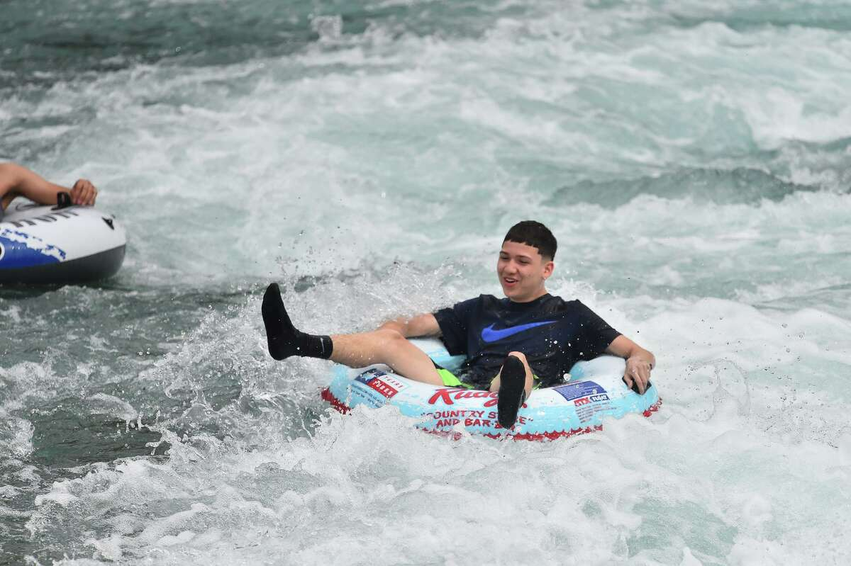 A tuber goes through the whitewater below the New Braunfels tube shoot Sunday as tubing season begins and slightly more normal spring break activities.