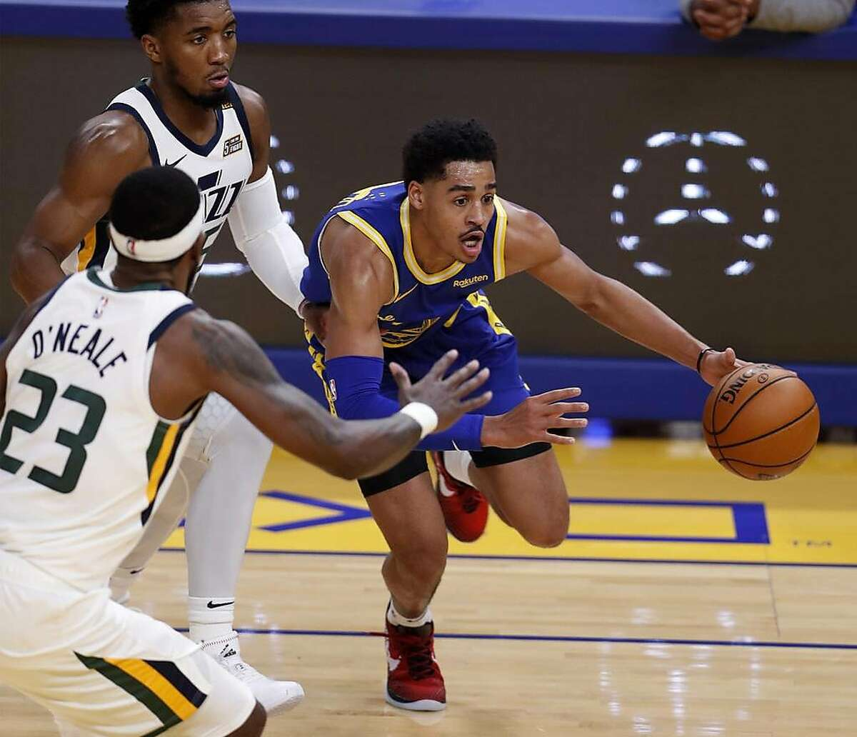 Warriors guard Jordan Poole drives around Jazz guard Donovan Mitchell (rear) during the second quarter of Golden State's victory at Chase Center.
