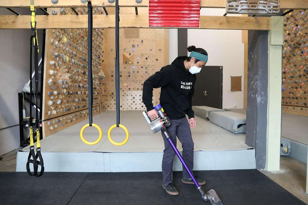 Alex Chuong, owner and operator of Oaktown Boulders in Oakland, vacuums as the climbing gym prepares for reopening after Alameda County was moved to the red tier.