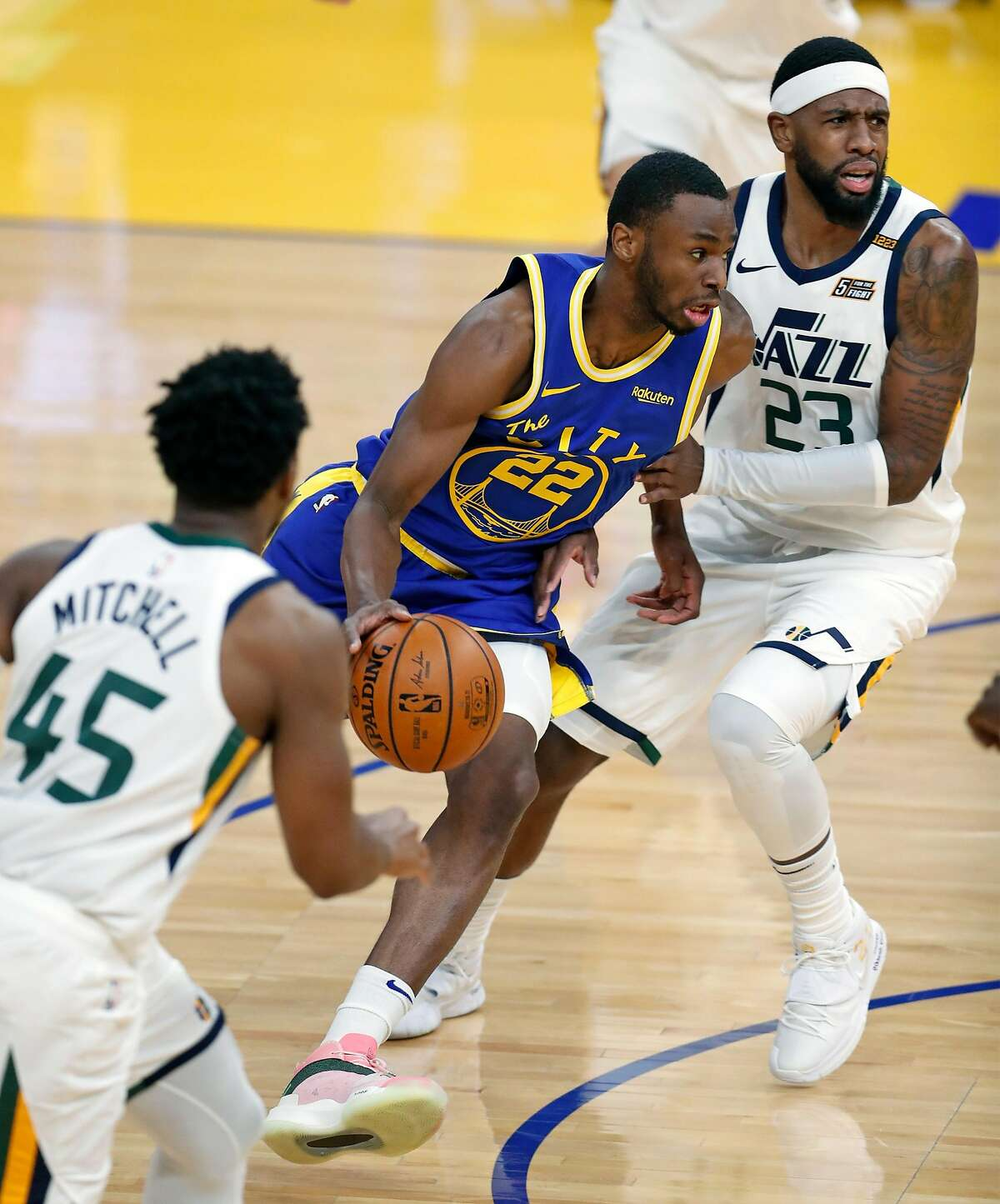 Warriors forward Andrew Wiggins dribbles between Utah's Royce O'Neale and Donovan Mitchell during the first quarter.