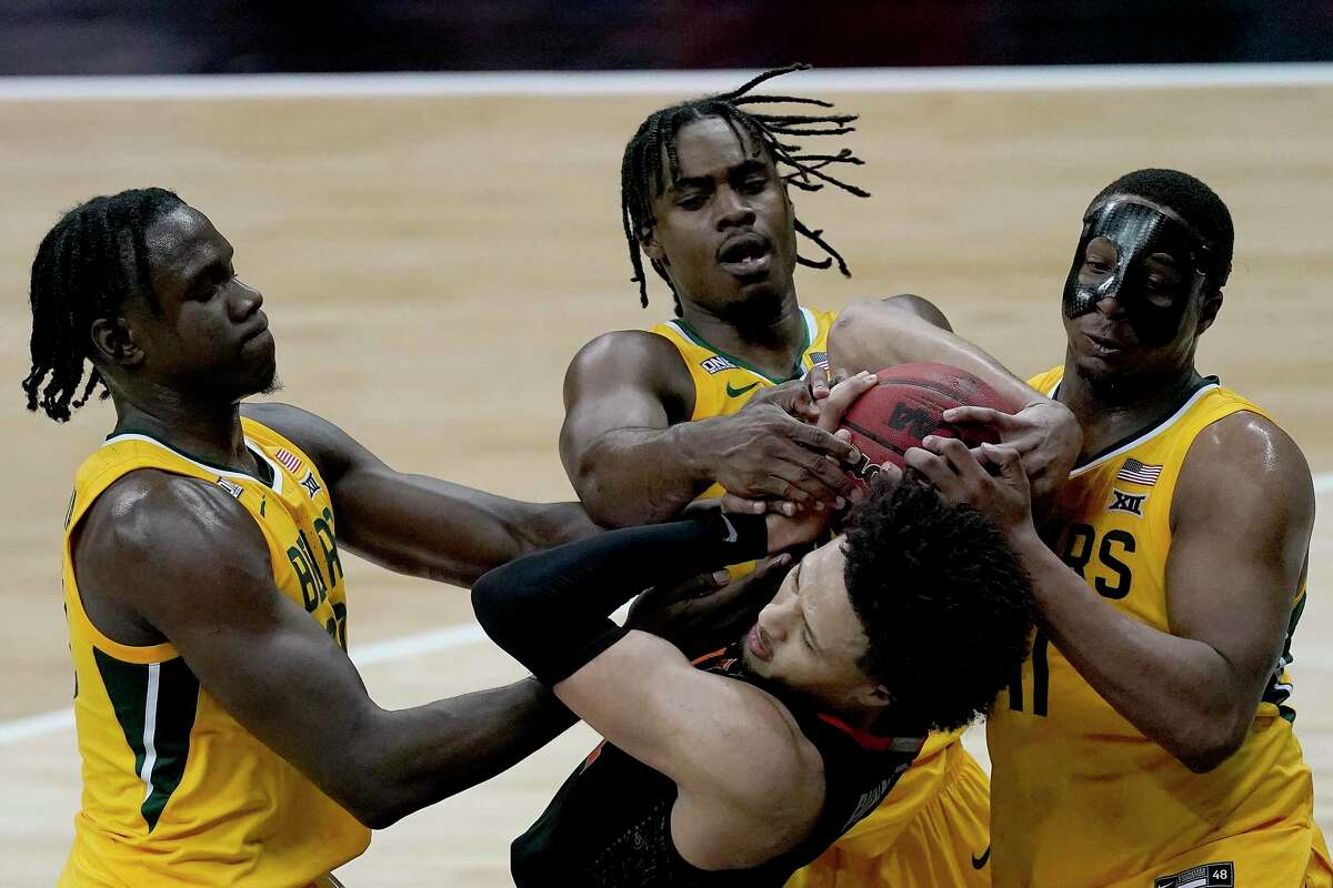 Oklahoma State's Cade Cunningham, front, battles for the ball with Baylor's Mark Vital, right, Davion Mitchell, center, and Jonathan Tchamwa Tchatchoua at the Big 12 tournament.