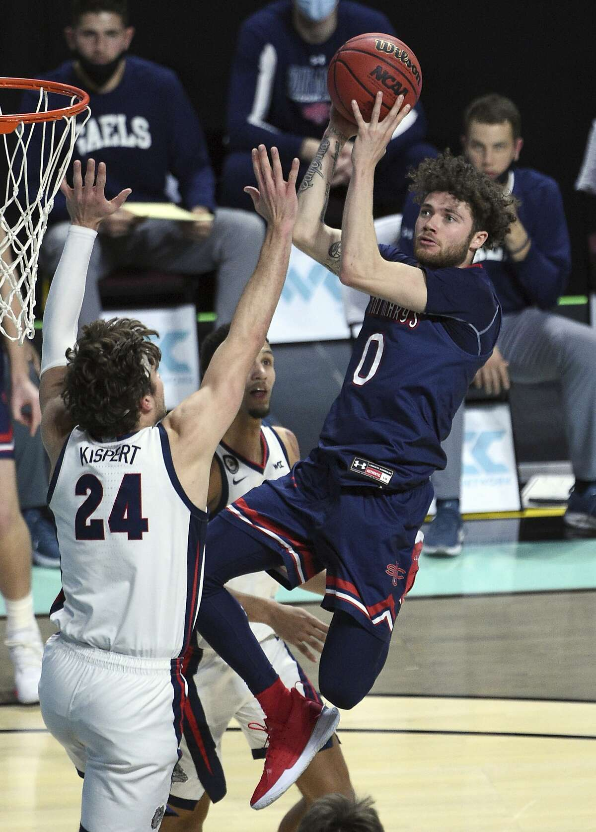 Saint Mary's guard Logan Johnson (0) shoots against Gonzaga forward Corey Kispert during the second half of an NCAA semifinal college basketball game at the West Coast Conference tournament Monday, March 8, 2021, in Las Vegas. (AP Photo/David Becker)