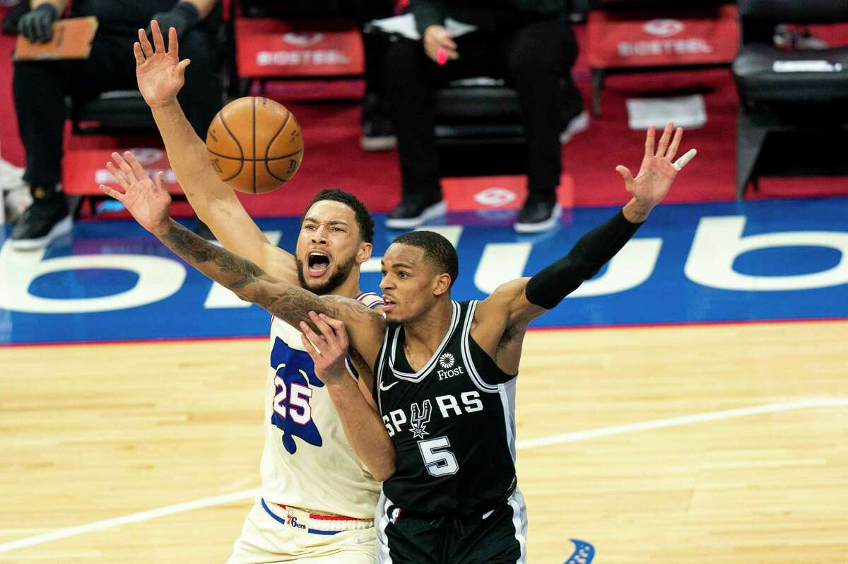 Philadelphia 76ers' Ben Simmons, left, reacts to getting fouled by San Antonio Spurs' Dejounte Murray, right, during the first half of an NBA basketball game, Sunday, March 14, 2021, in Philadelphia. (AP Photo/Chris Szagola)