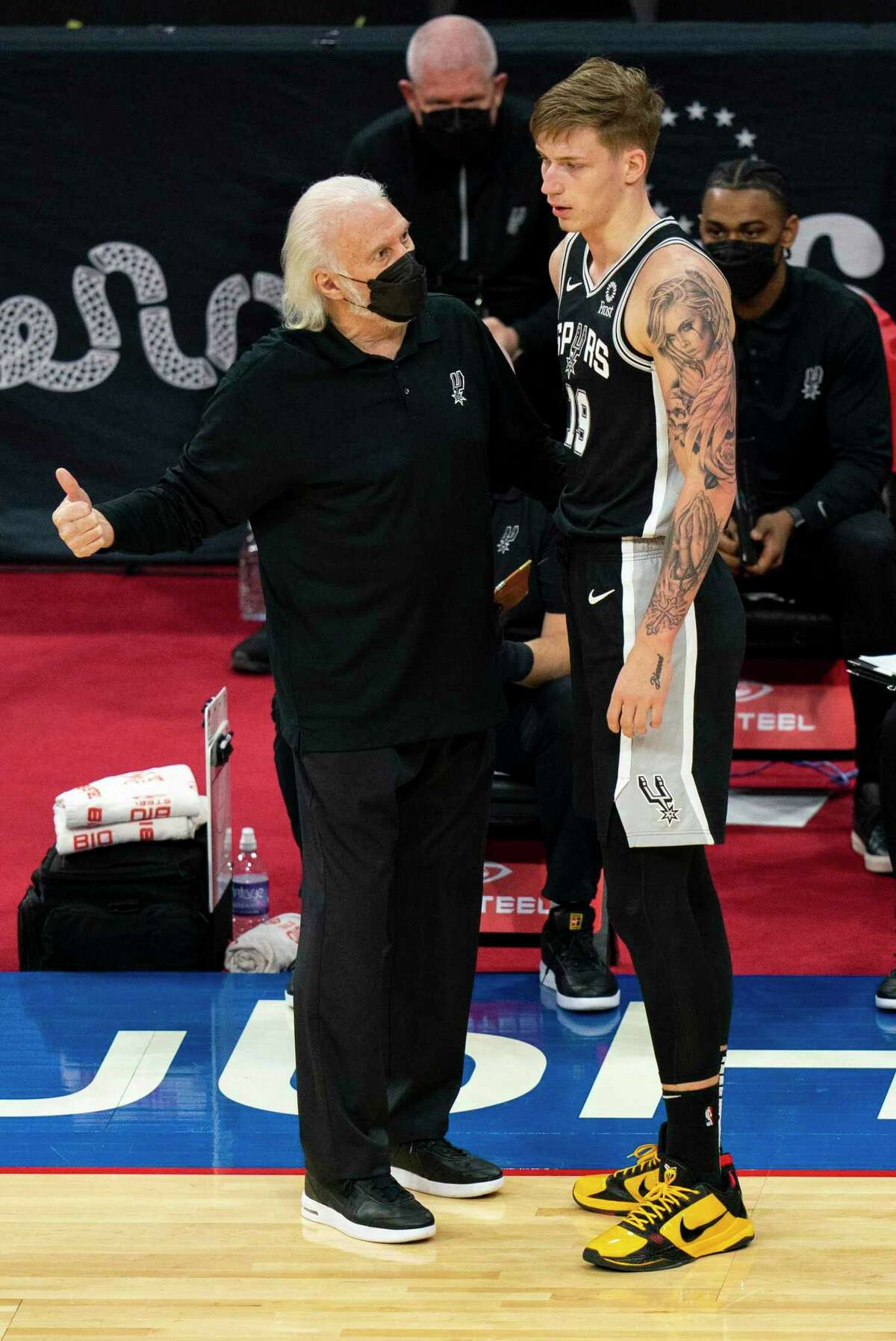San Antonio Spurs head coach Gregg Popovich, left, talks with Luka Samanic, right, during the second half of an NBA basketball game against the Philadelphia 76ers, Sunday, March 14, 2021, in Philadelphia. (AP Photo/Chris Szagola)