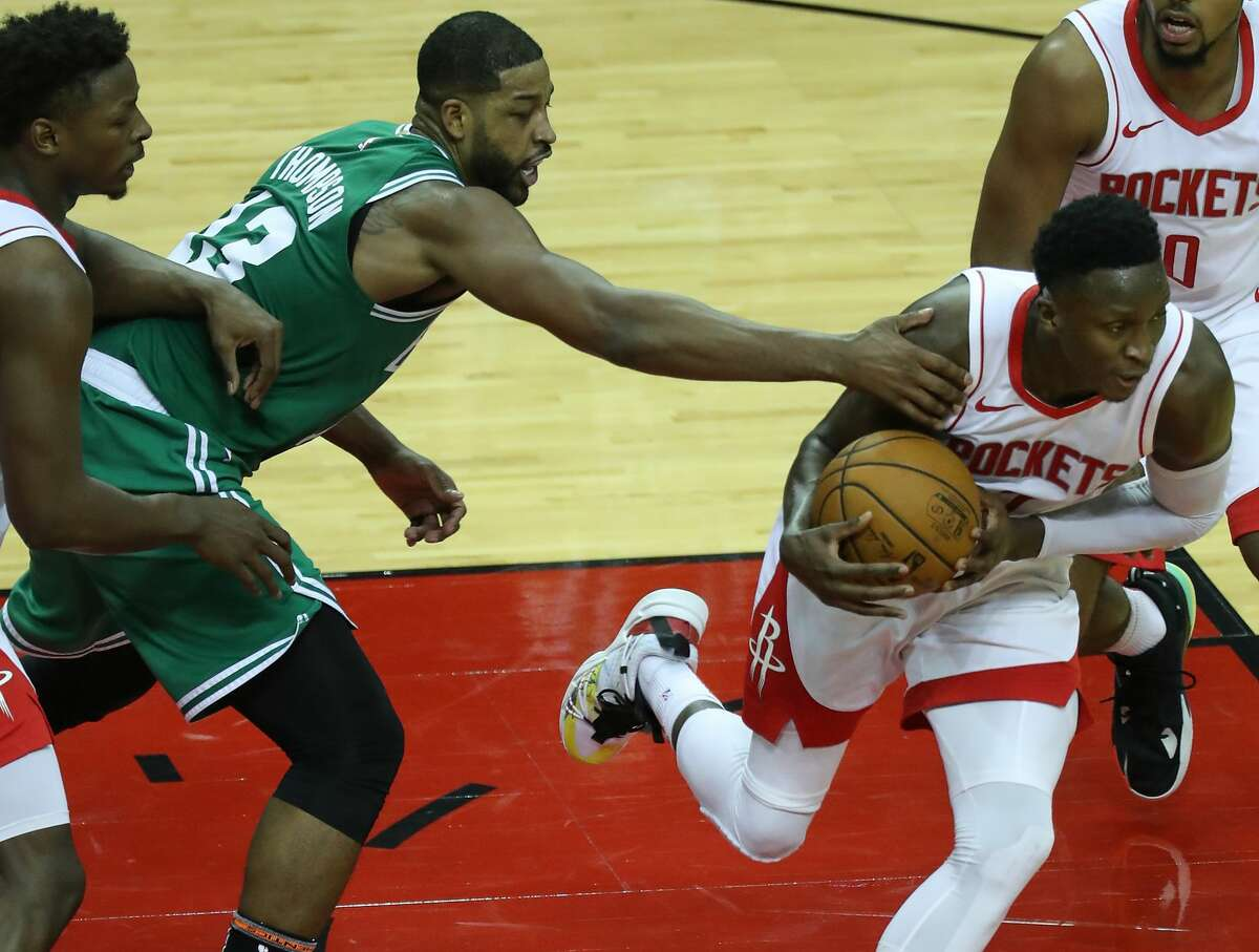 Boston Celtics forward Tristan Thompson (13) reaches out to try and stop Houston Rockets guard Victor Oladipo (7) as Oladipo picks up a loose ball during the second half of an NBA basketball game Sunday, March 14, 2021, in Houston.