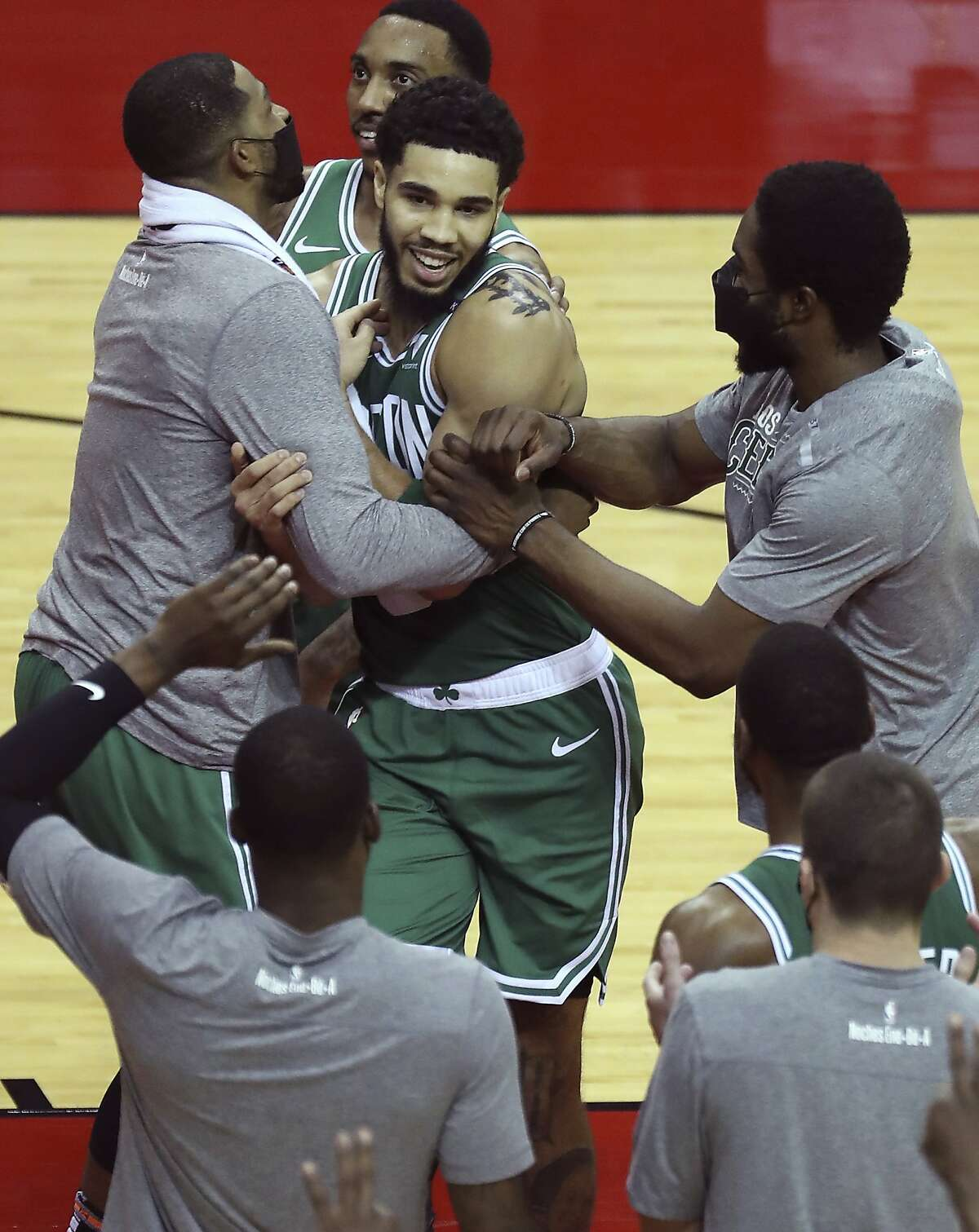 Boston Celtics forward Jayson Tatum (0) is hugged by teammates after he hit a three-point basket at the buzzer to end the third quarter against the Houston Rockets in an NBA basketball game Sunday, March 14, 2021, in Houston./Houston Chronicle via AP)