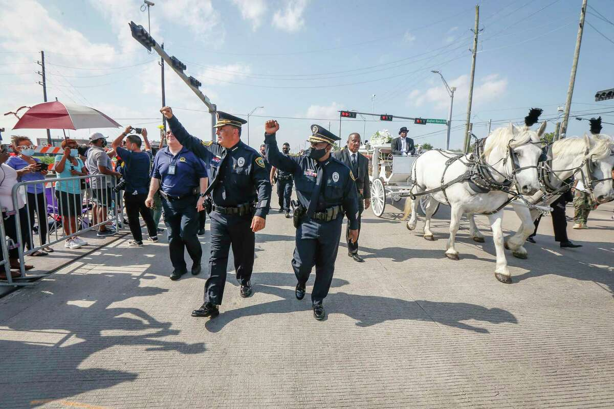 Houston Police Chief Art Acevedo and Assistant Chief of Police Lt. Troy Finner walk next to a horse-drawn carriage carrying the remains of George Floyd on the way to the Houston Memorial Gardens Tuesday, June 9, 2020, in Pearland .