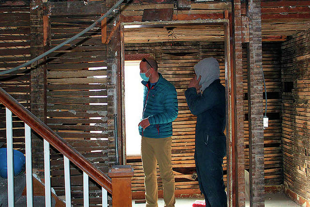 BlueEarth Deconstruction owner Steve Filyo and an employee survey a bedroom of a house in Naperville. The company is taking apart the house piece by piece so it can be preserved or reused.
