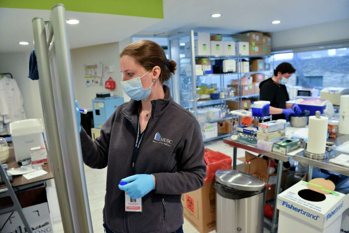 Scientist Kristina Andrijauskaite records data while Rafael Varaza preps a pig heart at Vascular Perfusion Solutions Inc. Sunday morning as testing continues on a new device that could allow donated human hearts to remain viable in transport for up to eight hours, twice as long as the current system.