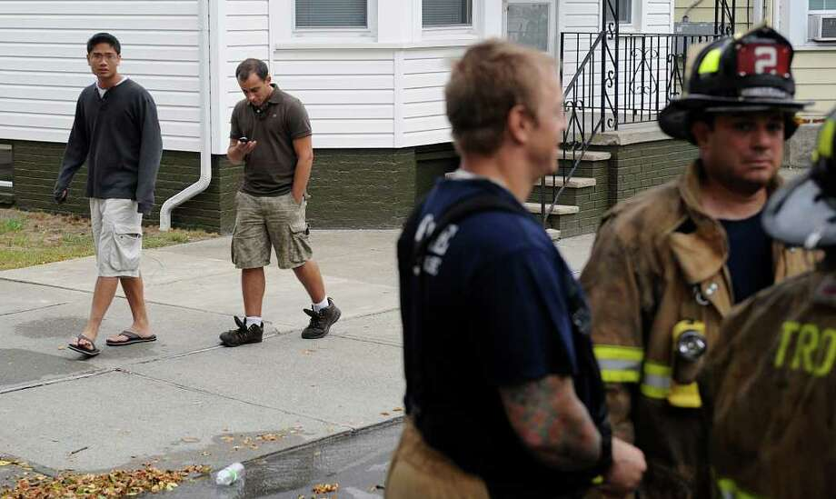 Daniel Bautista, of Smithtown, and Lane Waddell, of  Windsor, Conn., both RPI students, walk down 15th Street after an early morning fire Thursday forced from their Troy apartment.  (Skip Dickstein / Times Union) Photo: Skip Dickstein