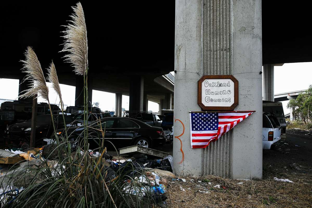 """A sign reading """"Oakland Humane Commons"""" and an American flag hang on a column at the Wood Street encampment in Oakland on Oct. 10, 2020."""