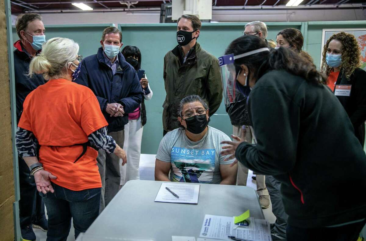 STAMFORD, CONNECTICUT - MARCH 14: A health worker prepares to administer a COVID-19 vaccine to an immigrant, as CT politicians speak to a volunteer on March 14, 2021 in Stamford, Connecticut. The non-profit Building One Community organized the event to administer the first dose of the Moderna vaccine to more than 350 people from the immigrant and undocumented communities. The vaccines were supplied by the federal Health Resources and Services Administration (HRSA). Vaccine recipients are due to return in April for their second dose. In background from L-R Ct. Governor Ned Lamont (D-CT), Senator Richard Blumenthal (D-CT) and Congressman Jim Himes (D-CT) speak with a volunteer. (Photo by John Moore/Getty Images)