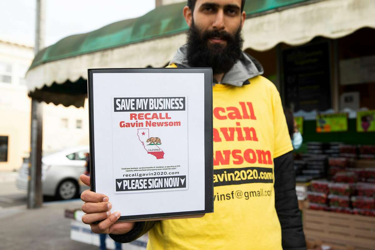 A volunteer with the Recall Gavin Newsom campaign who declined to share his name holds up a campaign sign while working to gather signatures from customers outside the 22nd & Irving Market.