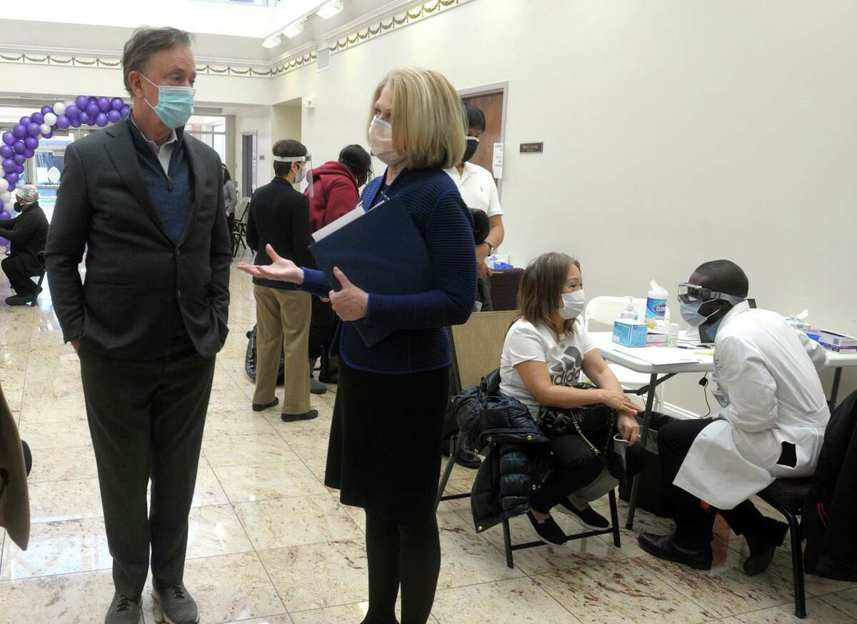 Gov. Ned Lamont, center, speaks with Yale New Haven Health CEO Marna Borgstrom on March 15, 2021, at a COVID-19 vaccination clinic in Bridgeport, Conn. Yale New Haven Health led all Connecticut employers for new job openings in the past few weeks, many of them at pay well above the state's $78,000 average household income.