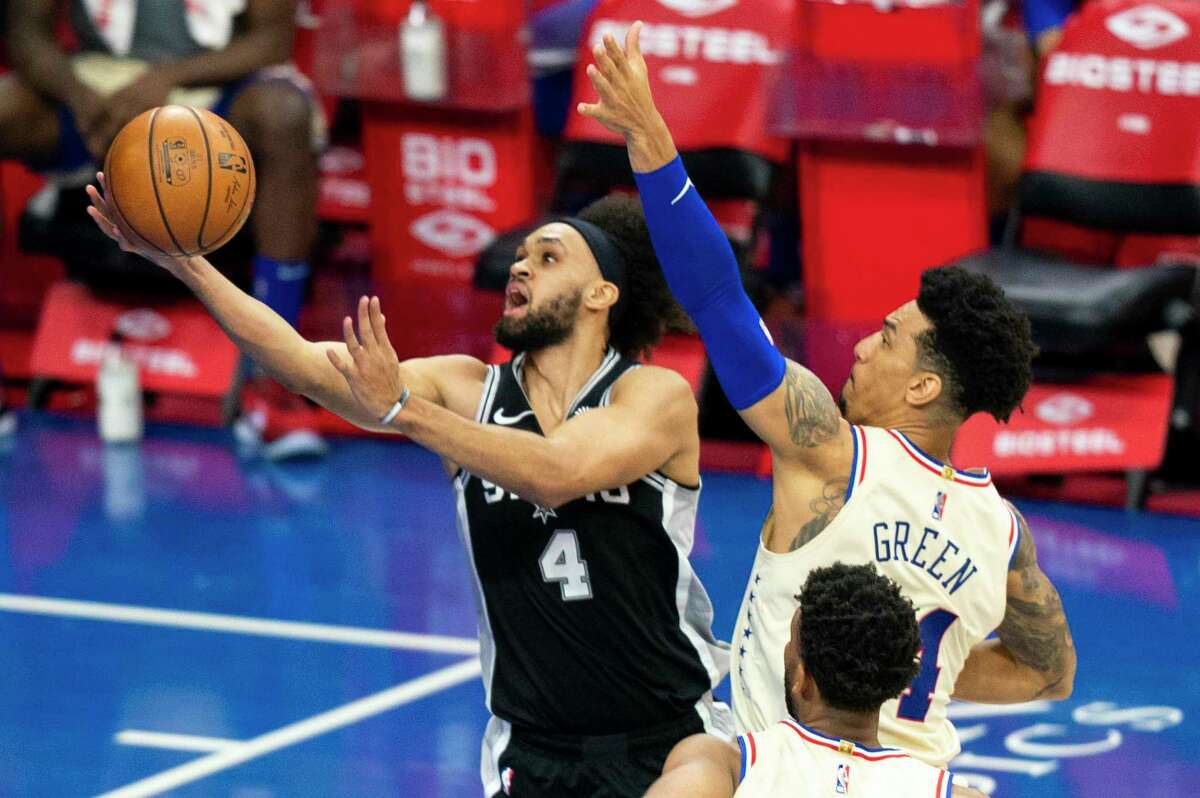 The Spurs' Derrick White goes up for the shot against the 76ers' Danny Green during the first half Sunday, March 14, 2021, in Philadelphia.