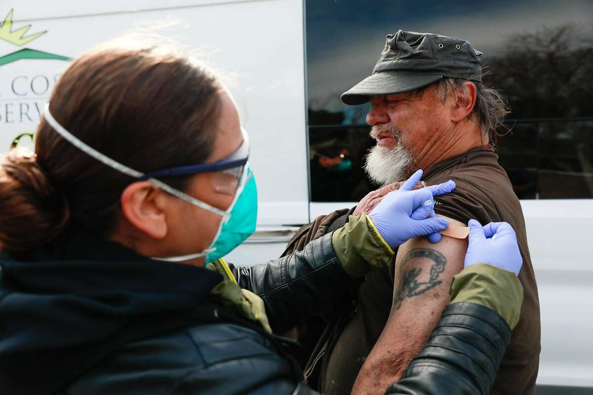 Christina Ramirez places a bandage on the newly vaccinated arm of homeless man Robert Clayton Kerfoot, 57, at a mobile clinic in Martinez.
