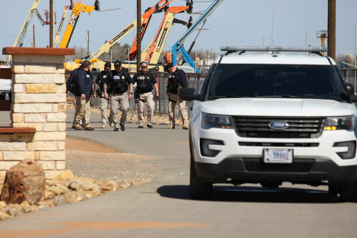 Department of Homeland Security officers are seen in the background of a temporary holding facility in Midrand County Monday, March 15, 2021. The holding facility was opened Sunday, March 14, 2021, for migrant juveniles from the southern border of the United States. (Mercedes Cordero/Midland Reporter-Telegram )