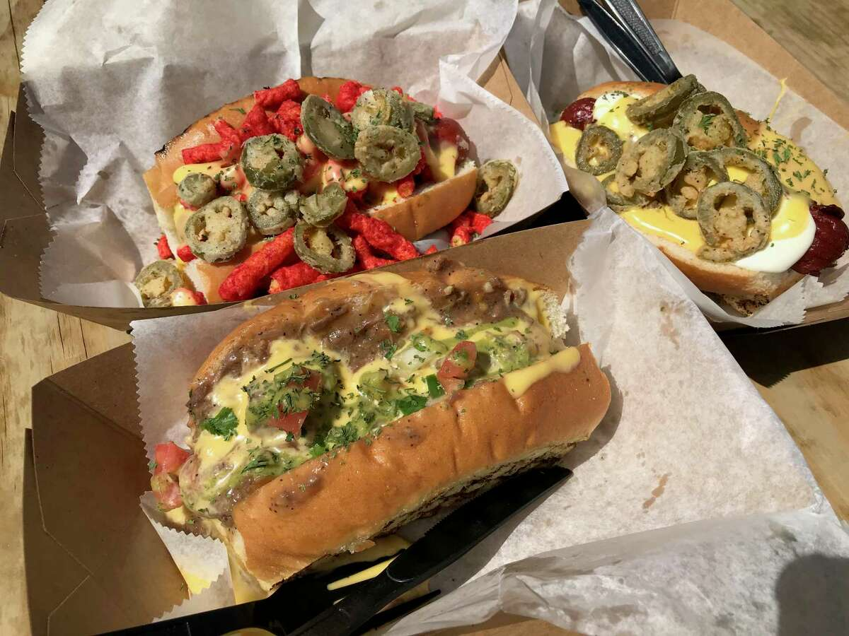 Hot dogs get a pure San Antonio treatment at The Dogfather including (clockwise from front) the Gotti Guisada and the Pop It Like It's Hot.