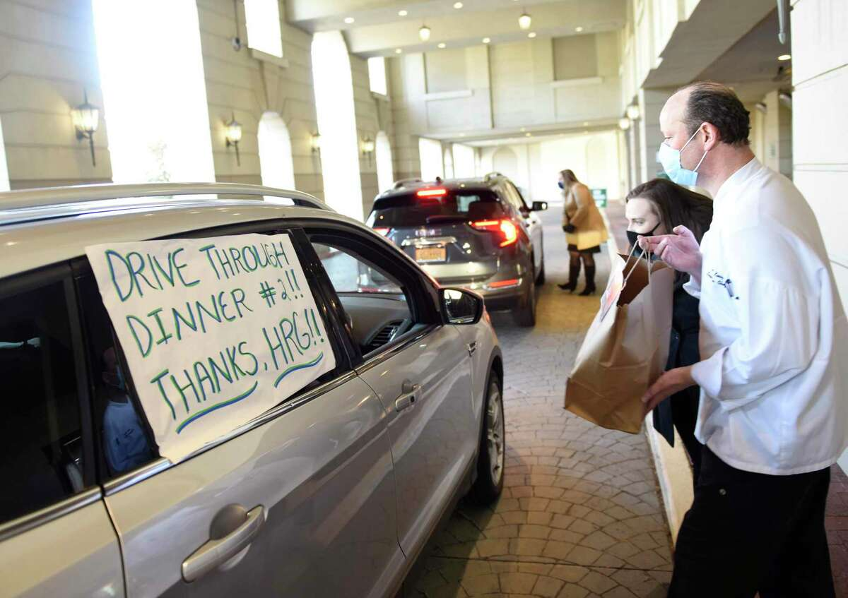 Executive Chef Huib Kooij and Director of Revenue Management Laura McLoughlin deliver a meal during a drive-thru dinner handout for current and former employees at the Hyatt Regency in Old Greenwich, Conn. Monday, March 15, 2021. Between 80 and 100 three-course meals were given away as a way to show appreciation to current employees working from home and laid off employees alike.