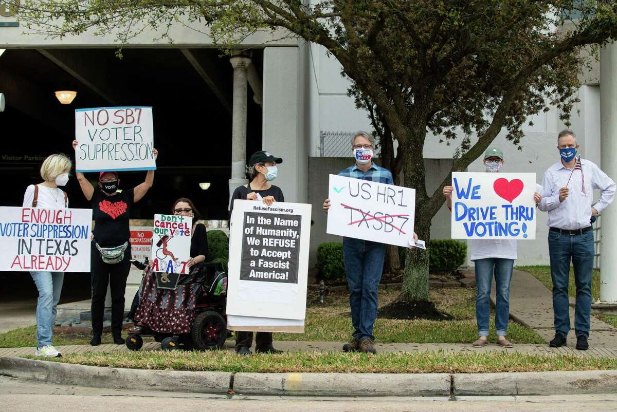 A group of demonstrators hold signs to protests a package of voting reforms outside Senator Paul Bettencourt District Office, where Gov. Greg Abbott held a press conference, on Monday, March 15, 2021, in Houston.