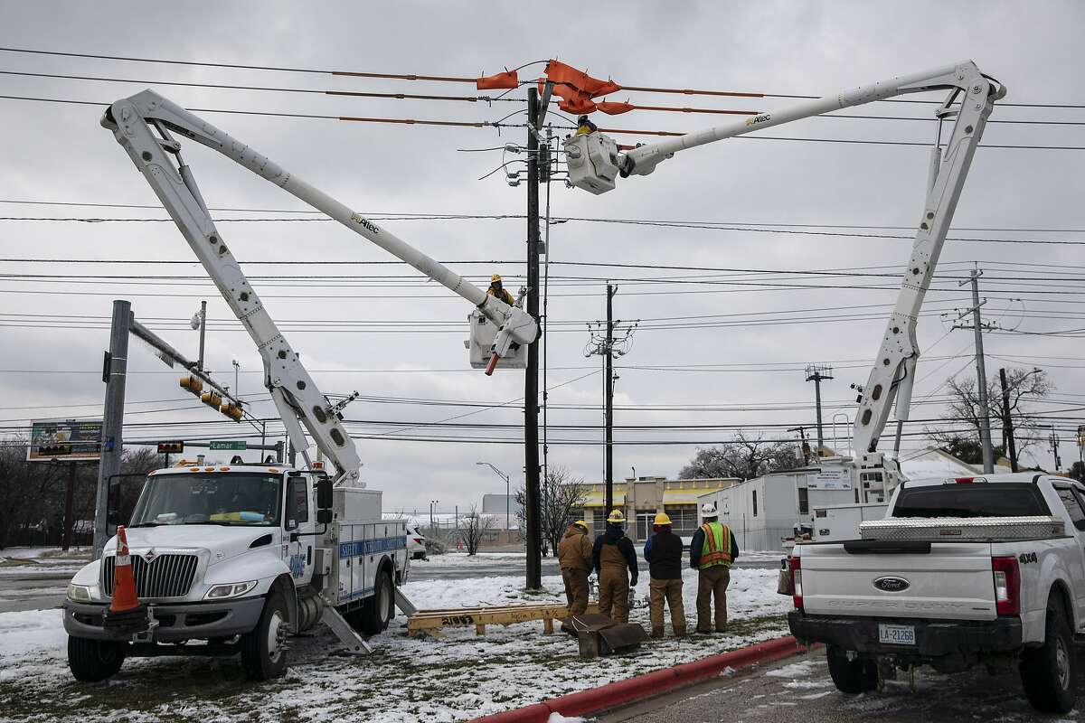 Utility workers repair a burnt-out switch in Austin, Texas, Thursday, Feb. 18, 2021.